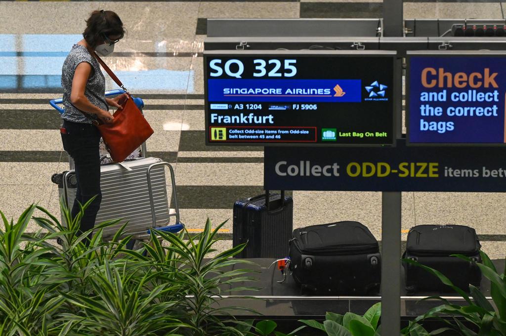 Một du khách trên chuyến bay SQ325 (chuyến đầu tiên đón khách theo chương trình VTL) của Singapore Airline đứng tại khu vực hành lý của sân bay Changi ngày 8/9. Ảnh: AFP