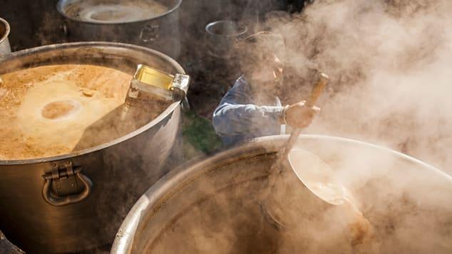 Một tình nguyện viên đang nấu đồ ăn phục vụ các tín đồ hành hương tại chùa Vàng. Ảnh: Lucas Vallecillos/AP