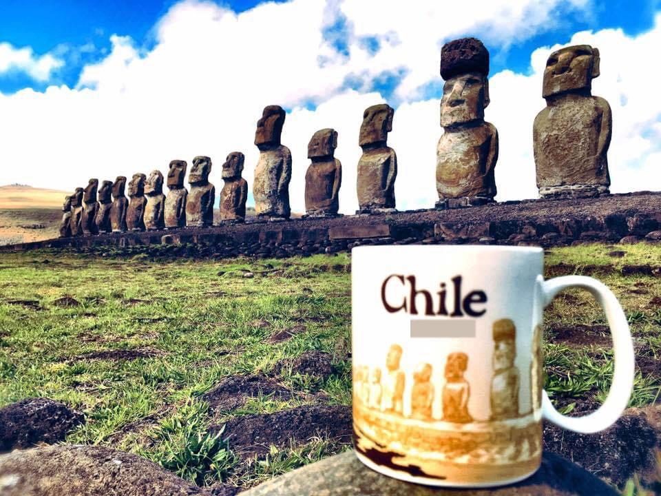 Anh Chương chụp ảnh cùng biểu tượng Moai tại Chile được in trên cốc. Ảnh: NVCC