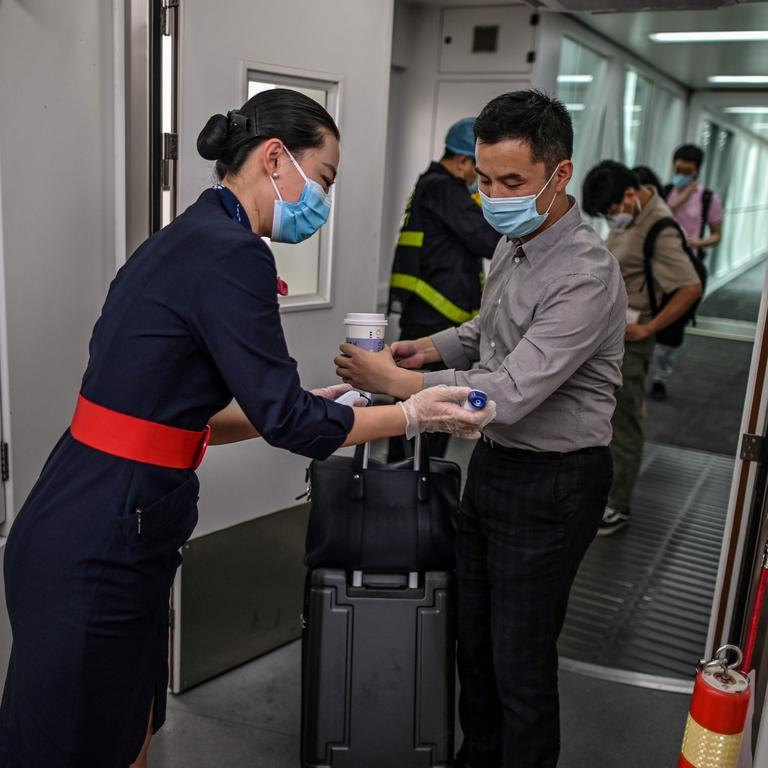 Tiếp viên đang kiểm tra nhiệt độ của hành khách. Ảnh: Hector Retamal/AFP