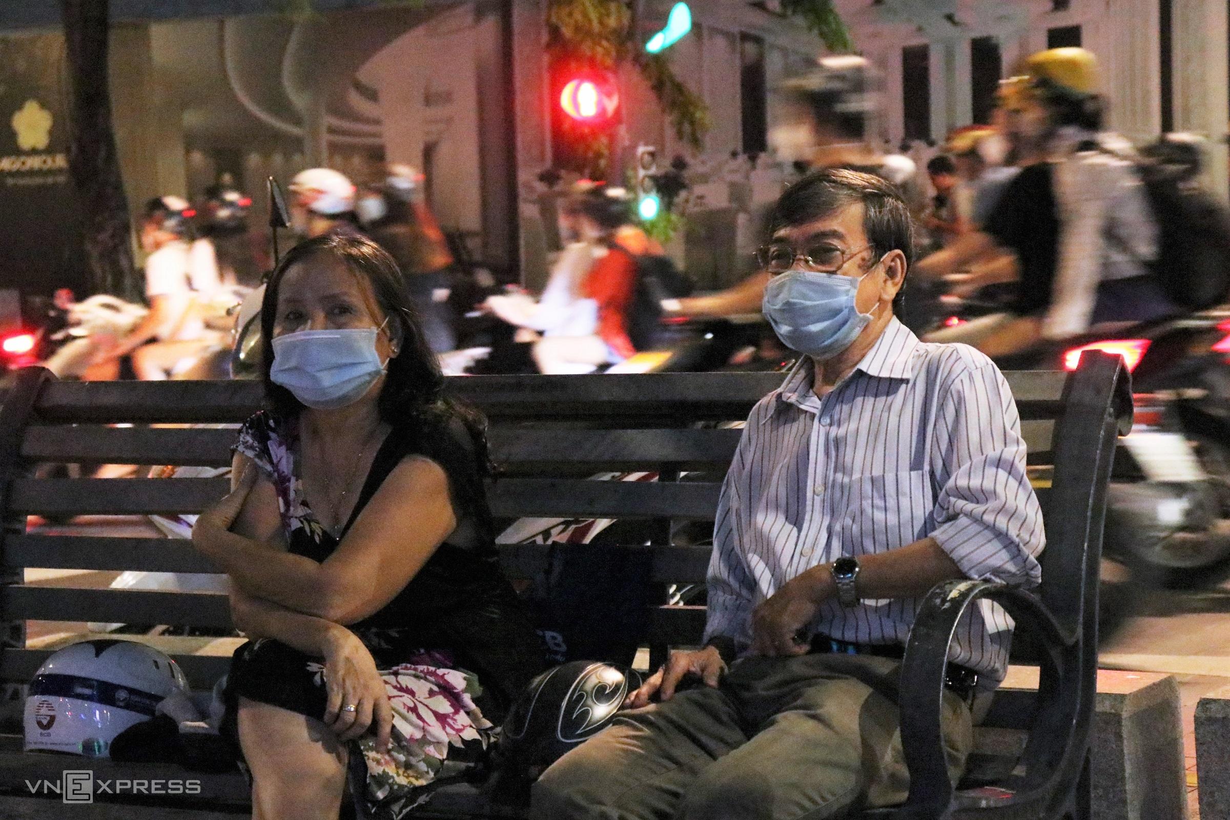 Vợ chồng chú Thạnh, cô Hoa ngồi ở phố đi bộ Nguyễn Huệ tối 10/10. Ảnh: Huỳnh Nhi